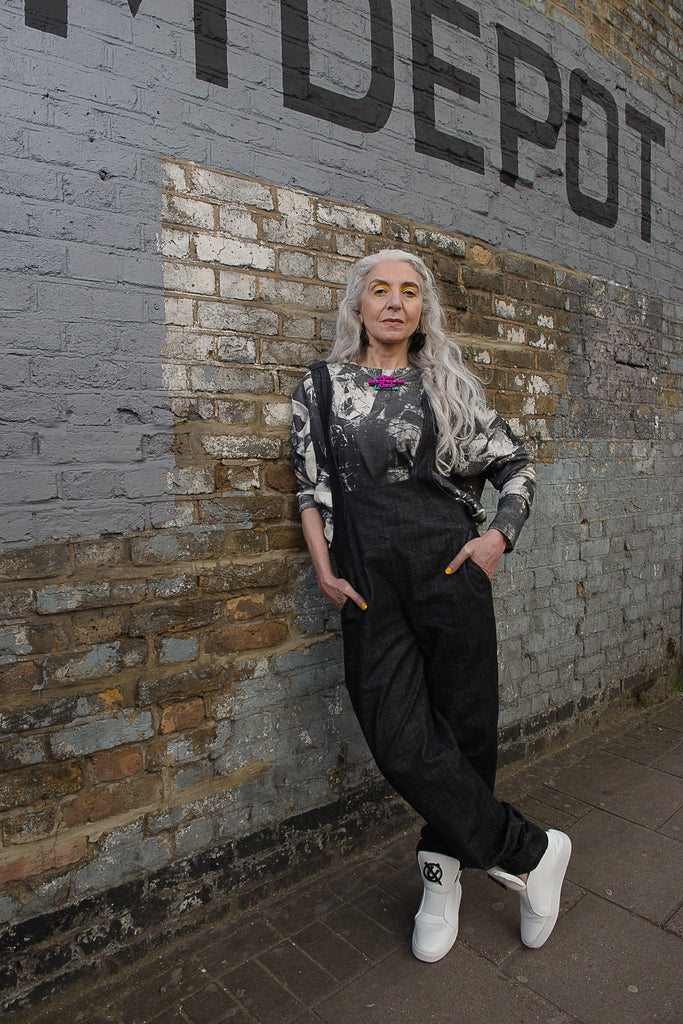 Model Alex B in phannatiq organic cotton denim dungarees and london print organic cotton Oscar top standing by a wall