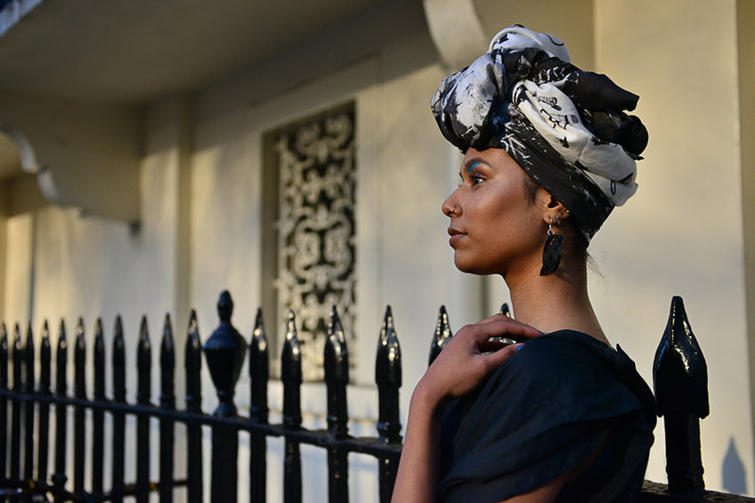 Fahema in a phannatiq cat stripes headscarf and black phannatiq florence dress standing by a wrought iron fence in West London staring into the middle distance