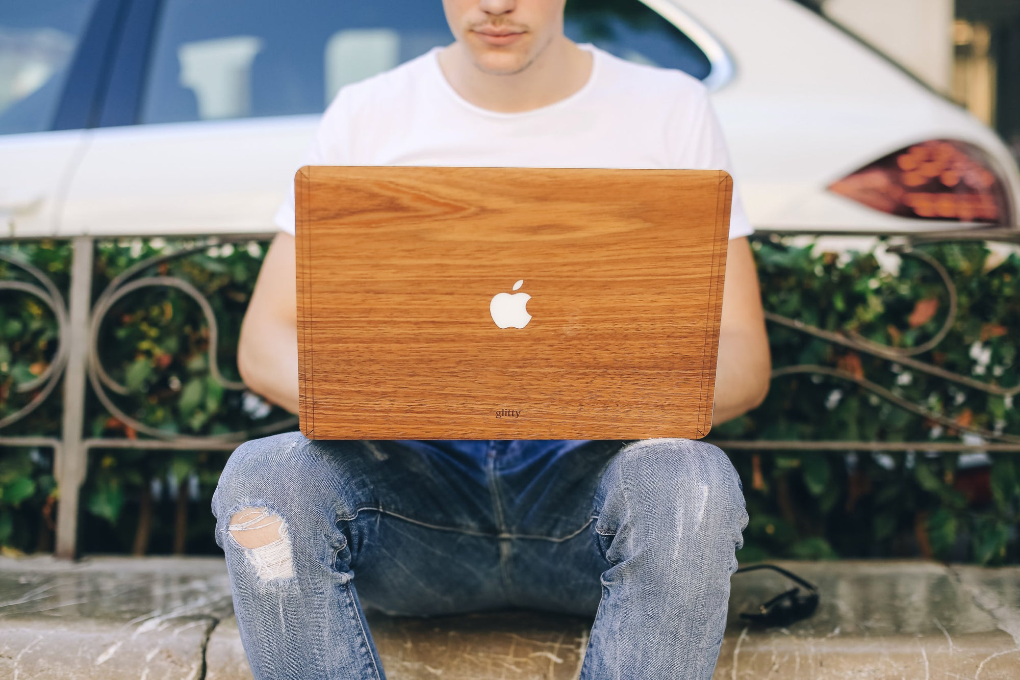 Guy with ripped jeans sitting on the sidewalk working on his MacBook with a Glitty Walnut cover