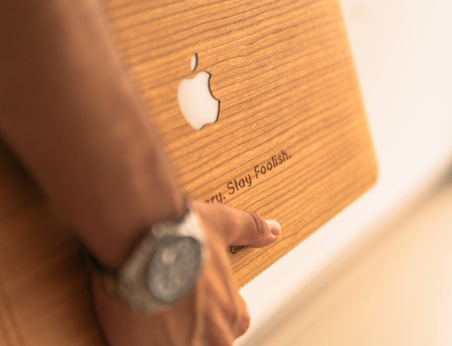 Closeup photo of a hand with a luxury watch holding a MacBook Air with a handmade Glitty Cherry Wood cover