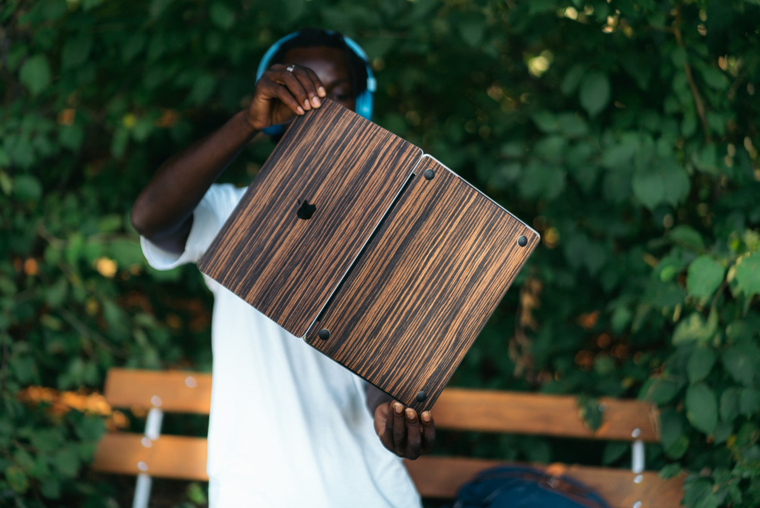 Cool guy with headphones on opening his MacBook Pro to show the top and bottom Glitty Ebony wood cover. He is standing outside in nature in a park.