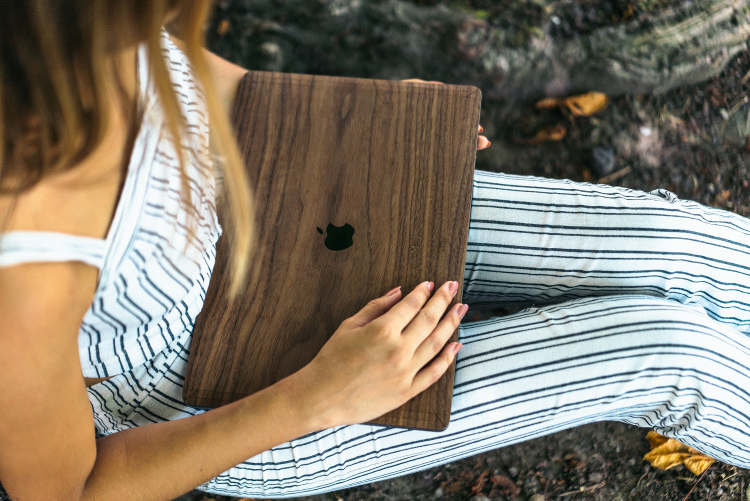 Girl holding her MacBook Pro on her lap, with her hand on her Glitty Walnut Wood Cover