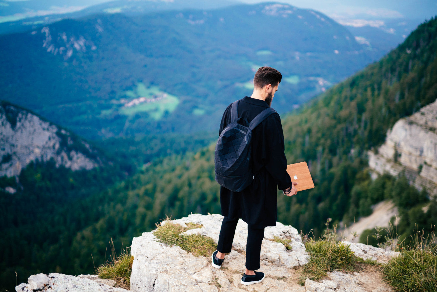 Stylish man with a backpack on is looking down from the top of a mountain holding a MacBook with Glitty Wood Cherry Cover