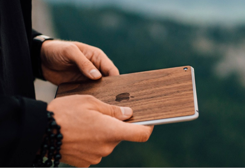 Hands holding an iPad with a Glitty Walnut cover, in the background the natural landscape is blurry