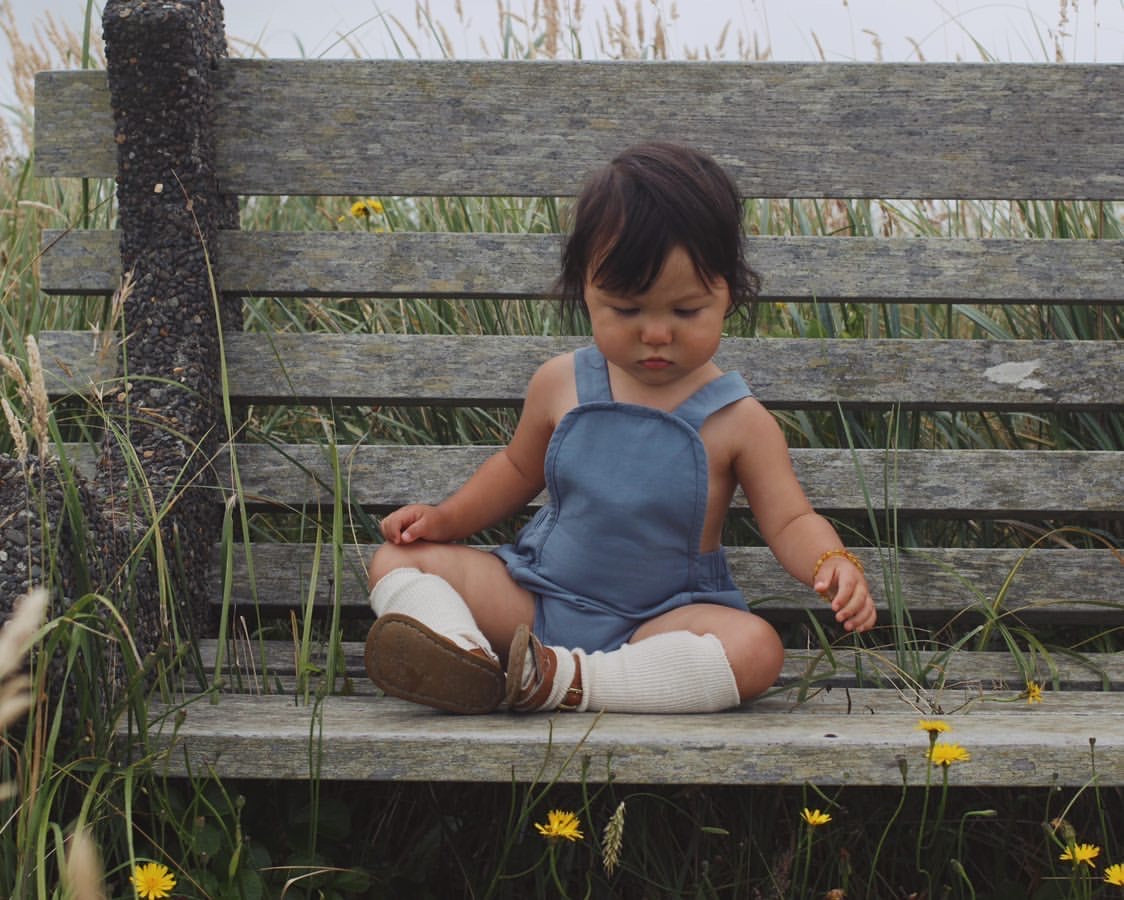 Baby sitting on bench in a denim blue organic sunsuit