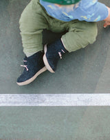 Baby sitting down wearing green pants and charcoal Glerups wool baby boots