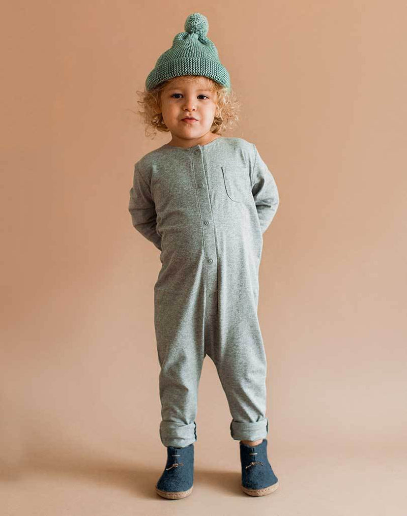 Baby wearing a gray playsuit, blue beanie and denim Glerups Wool Baby Boots