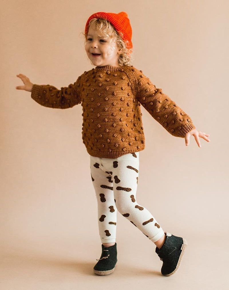 Baby wearing a brown popcorn sweater, peanut leggings and forest green Glerups Wool Baby Boots