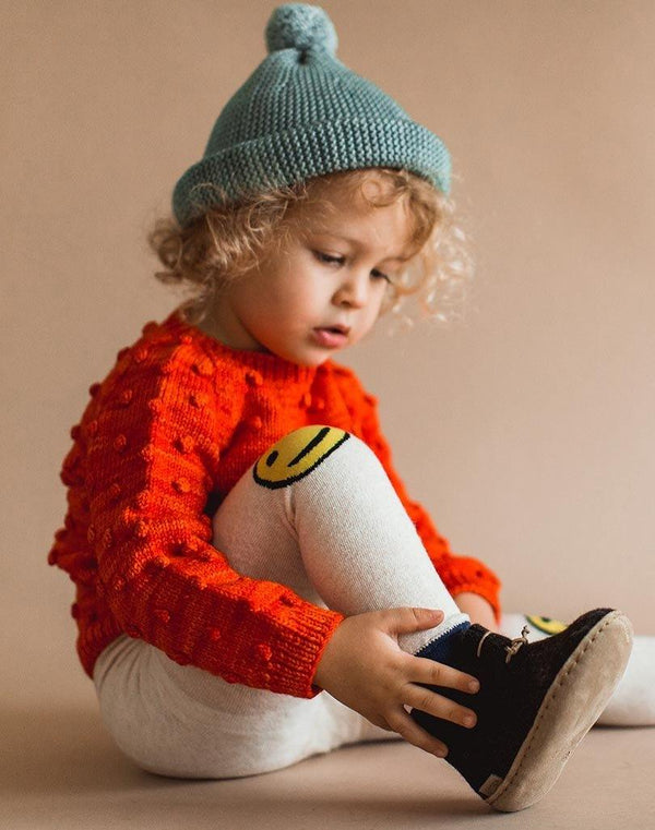 Baby sitting down wearing a blue beanie, red sweater, smiley leggings and charcoal Glerups wool baby boots