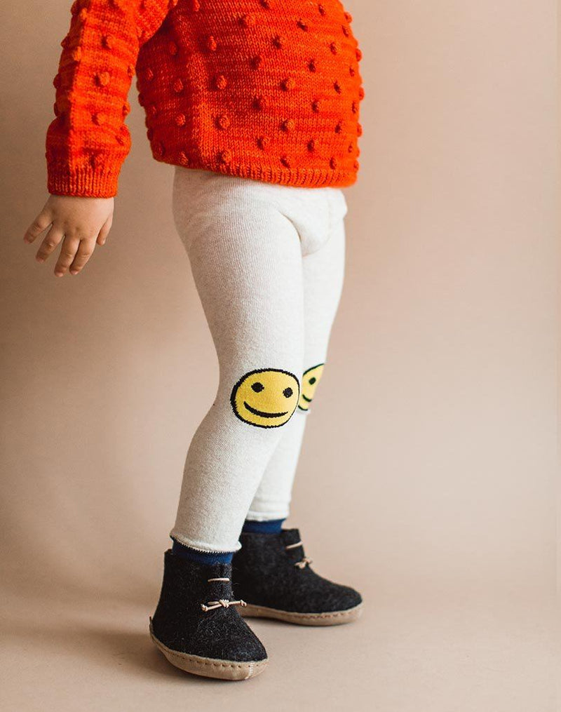 Baby wearing red popcorn sweater, smiley leggings and charcoal Glerups wool baby boots