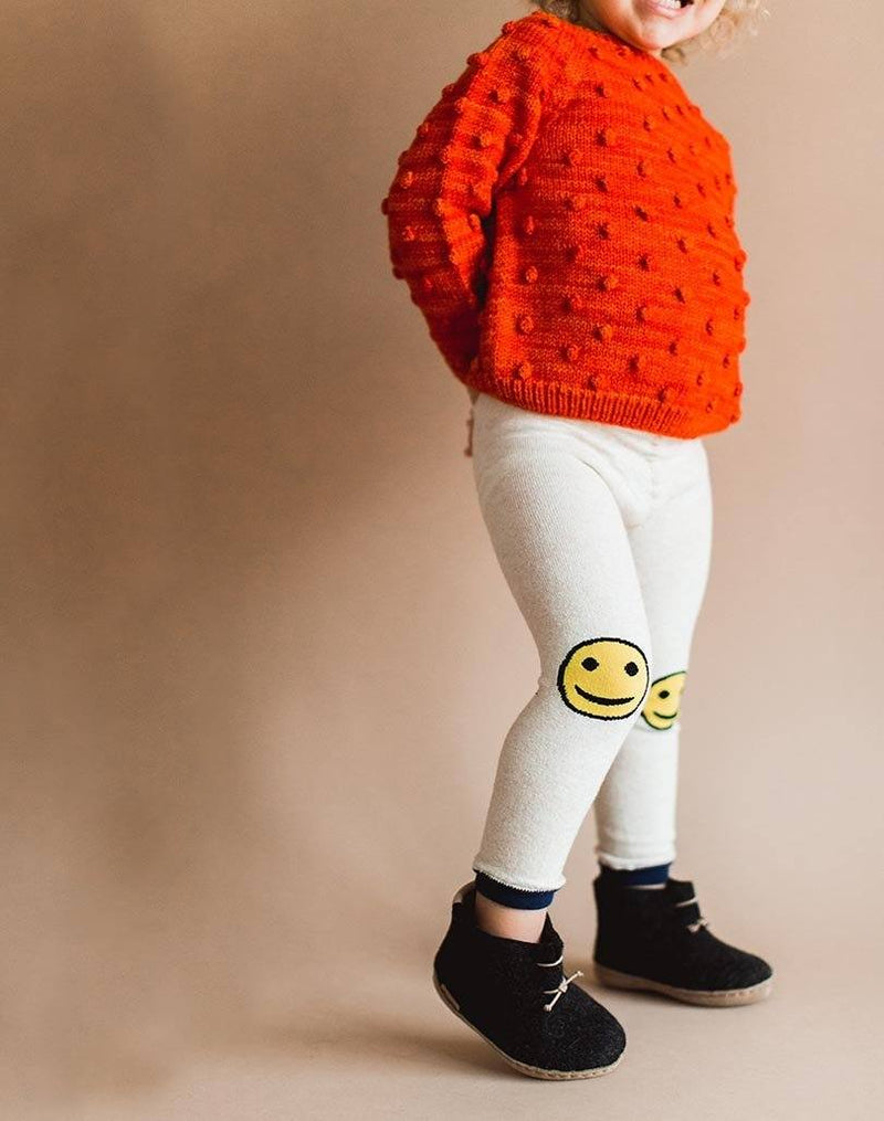 Baby showing off his red popcorn sweater, smiley leggings and charcoal Glerups wool baby boots