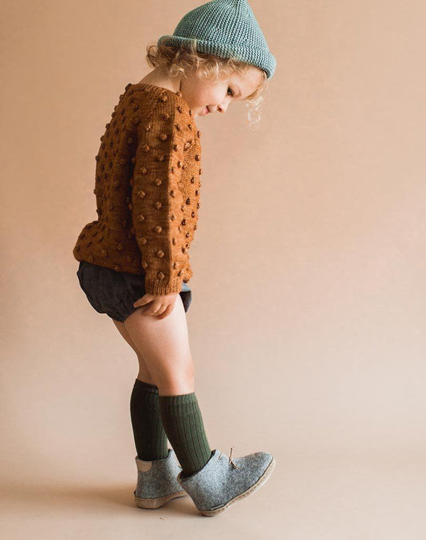 Baby wearing knee socks and grey Glerups Wool Baby Boots