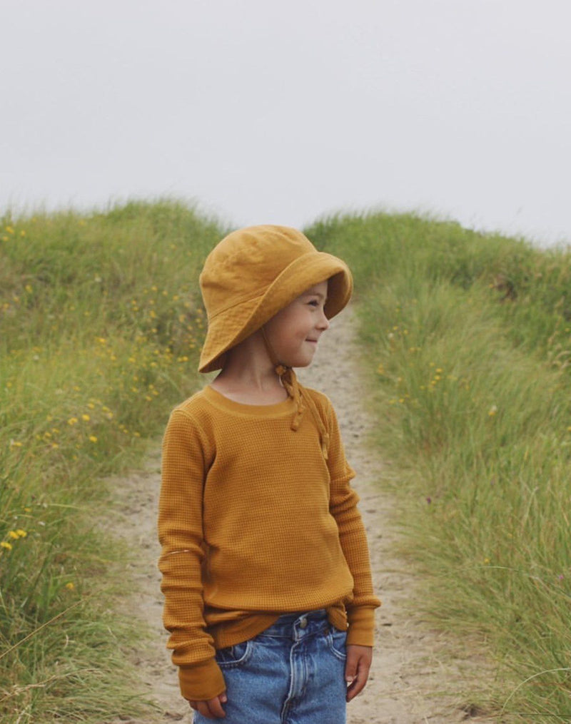 Kid walking on a sandy path wearing a turmeric colored sun hat and matching long-sleeved waffle top