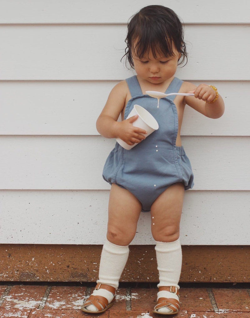 Baby spilling vanilla ice cream out of a cup wearing the Noble Sun Suit in Moon Blue