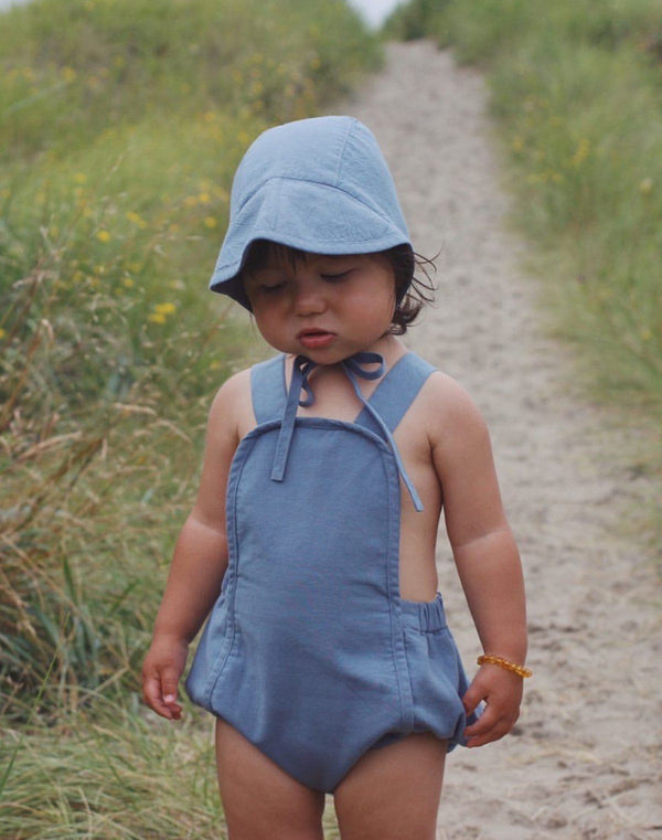 Baby on sandy path wearing a moon blue colored brimmed bonnet and sun suit by Noble