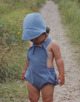 Baby walking on sand path wearing a moon blue brimmed bonnet and matching blue sun suit