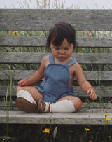 Baby sitting on a bench wearing the Noble Sun Suit in Moon Blue with white knee socks and sandals
