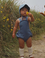 Baby picking yellow flowers in blue sunsuit and brimmed bonnet