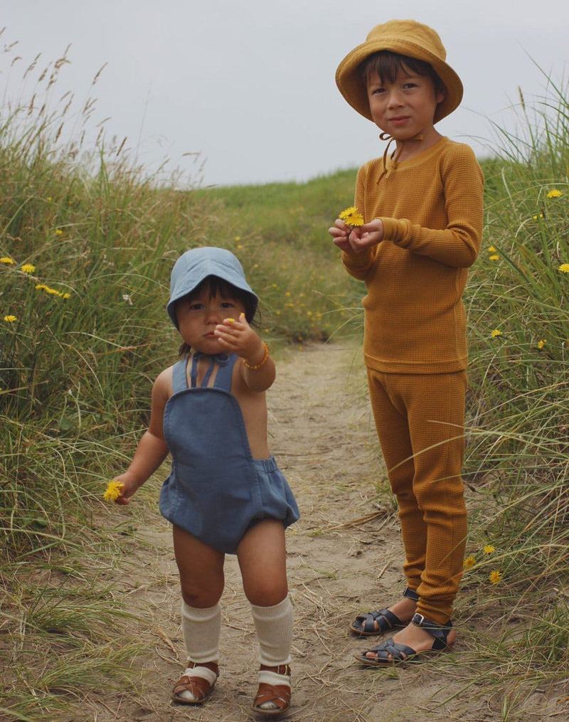 Two kids picking flowers at the beach wearing monotone blue brimmed bonnet and sun suit as well as monotone turmeric sun hat and waffle long-sleeve set
