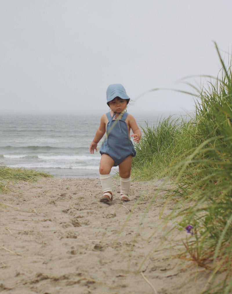 Baby walking on beach wearing a moon blue brimmed bonnet and sun suit with knee socks and sandals