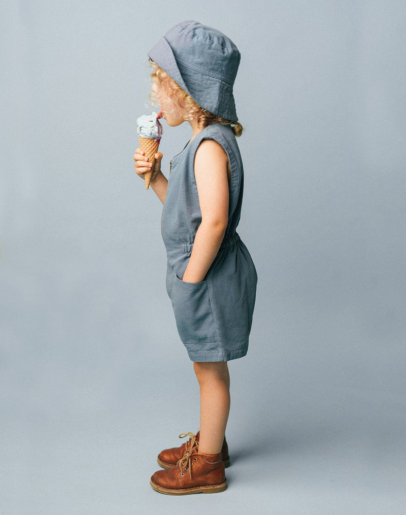 Side view of kid eating an ice cream cone wearing a blue moon sun hat and matching colored tank suit from Noble