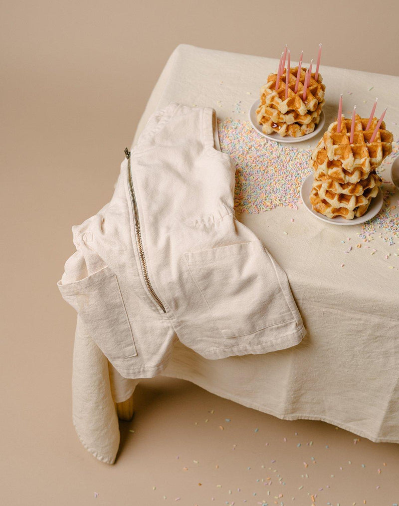 Nobe Tank Suit in Oat Milk color draped over a table with stacks of waffles and sprinkles