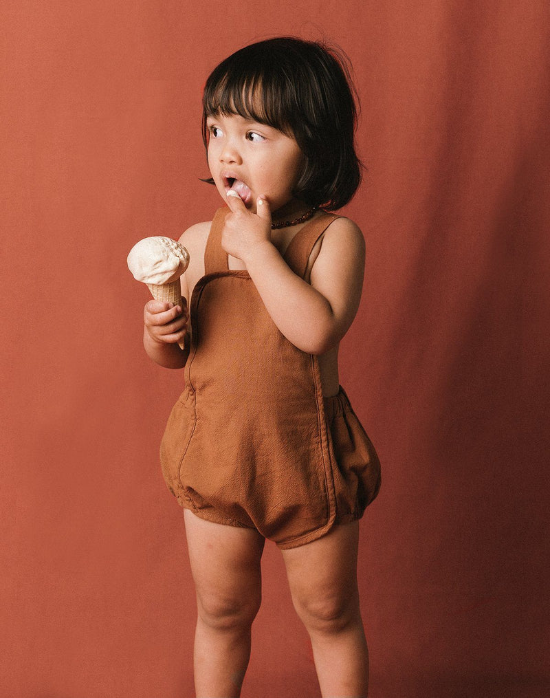 Baby eating an ice cream cone wearing the Noble Sun Suit in Cinnamon color