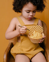 Baby eating ice cream out of a waffle bowl wearing the Noble Sun Suit in Turmeric color