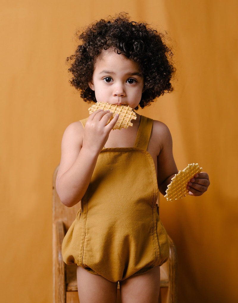 Baby eating waffle wafers wearing the Noble Sun Suit in Turmeric color