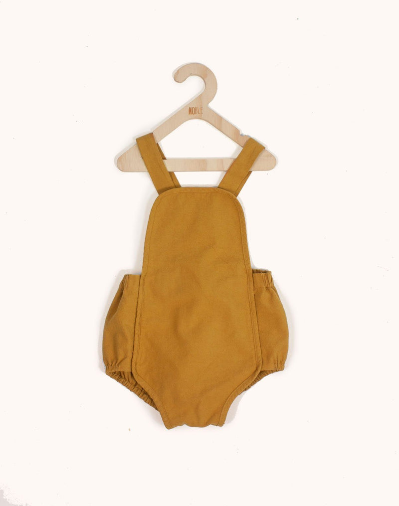 Noble Sun Suit in Turmeric color hanging from a kids hangar