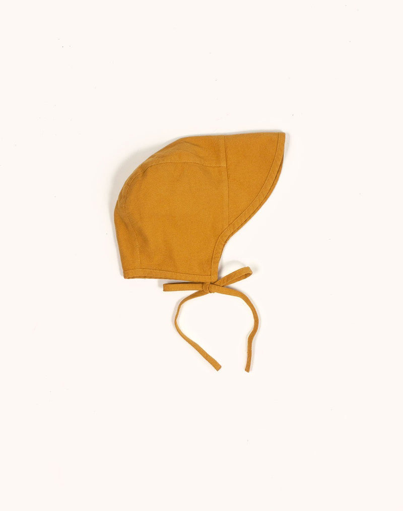 Noble Brimmed Bonnet in Turmeric color tied in a bow