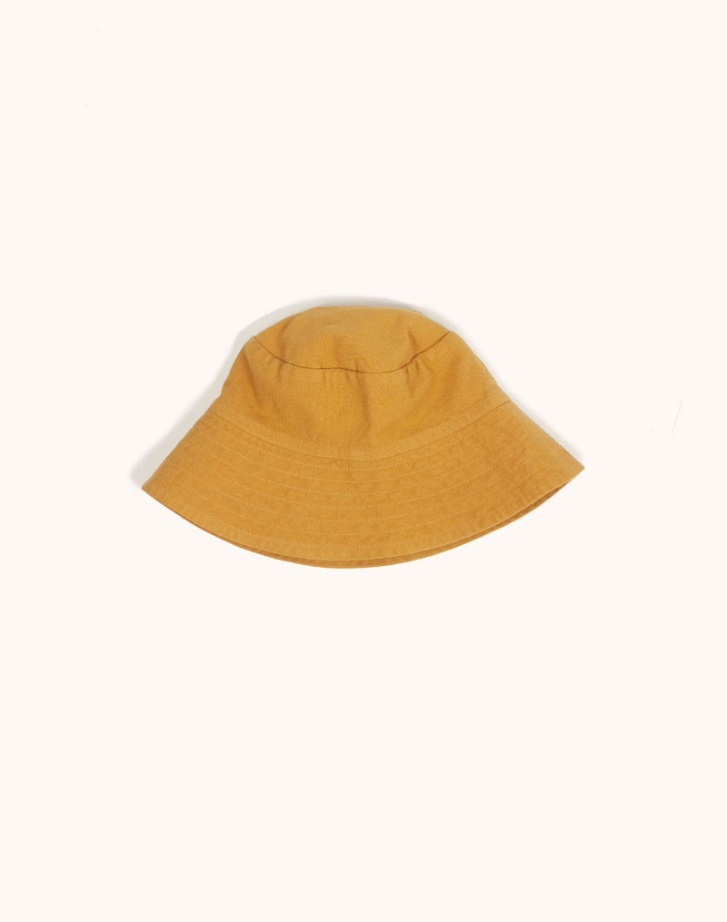Noble Sun Hat in Turmeric color with strings tucked under