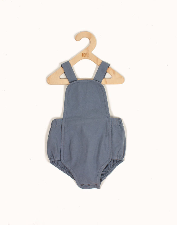 Noble Sun Suit in Moon Blue color hanging from a kids hangar