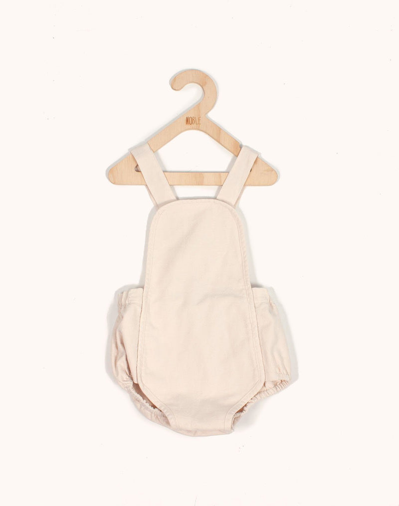 Noble Sun Suit in Oat Milk color hanging from a kids hangar