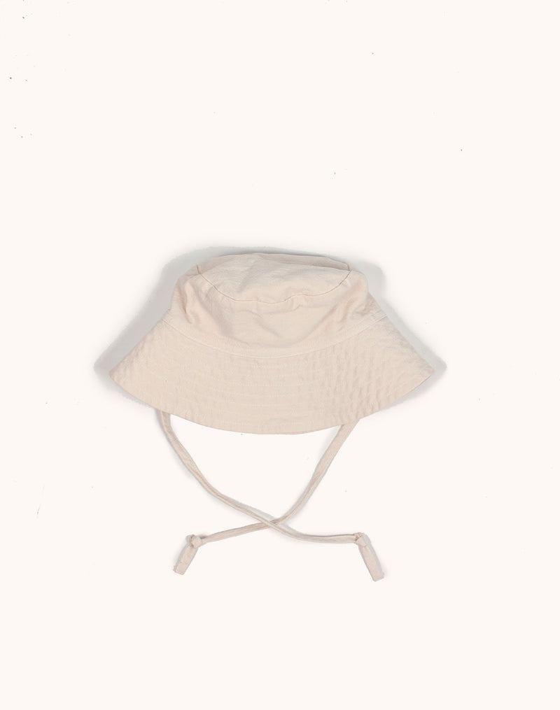 Noble Sun Hat in oat milk color with strings hanging low