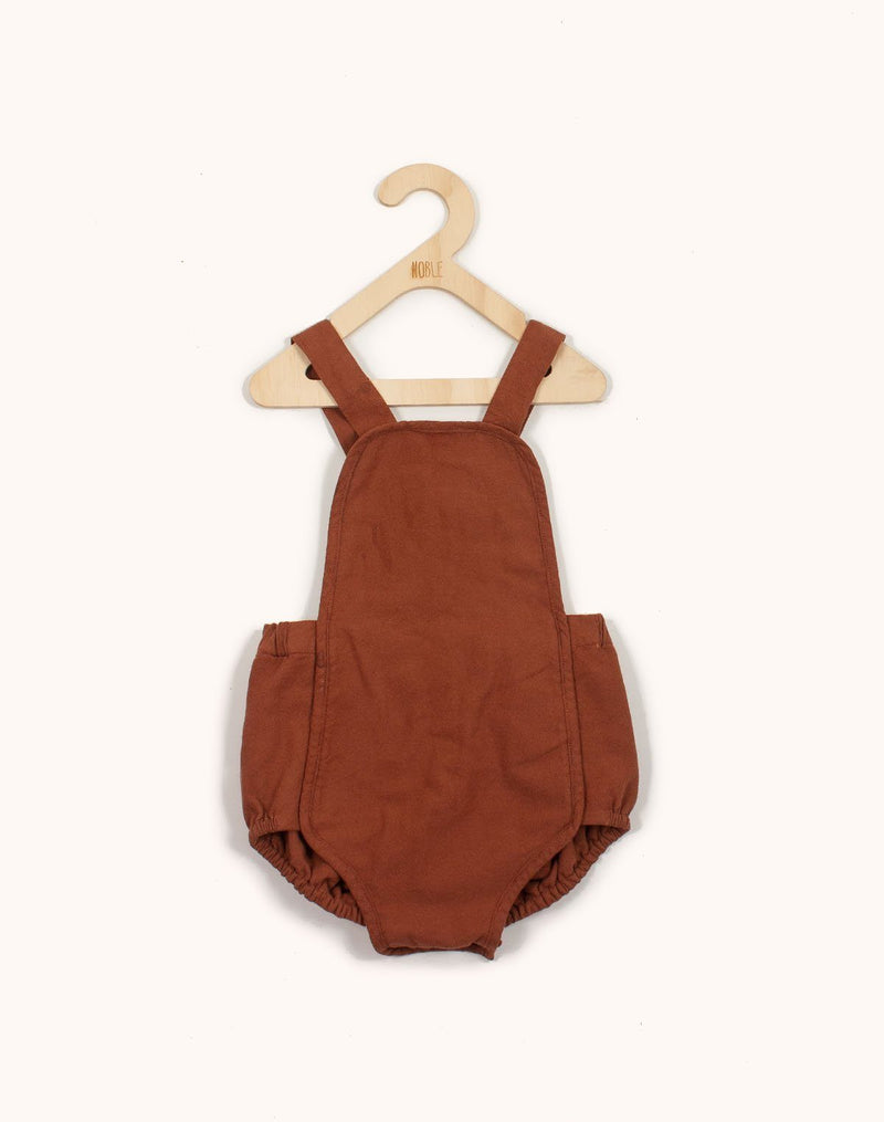 Noble Sun Suit in Cinnamon color hanging from a kids hangar