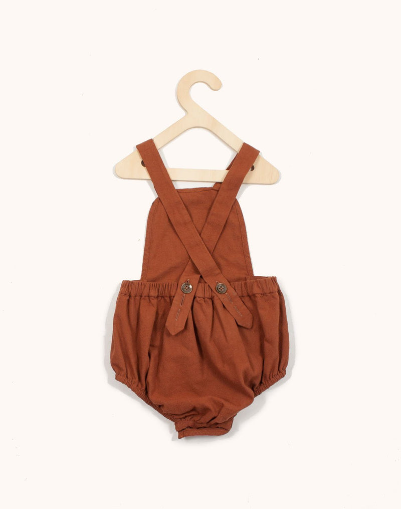 Back of the Noble Sun Suit in Cinnamon color hanging from a kids hangar