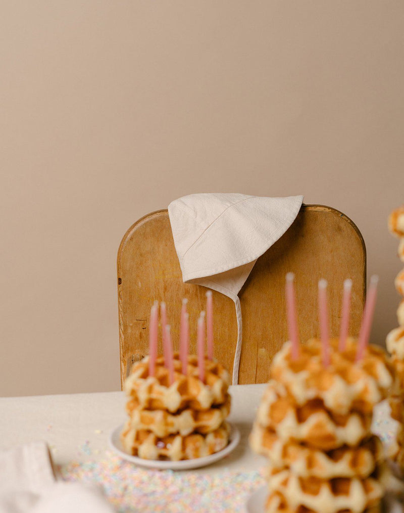 Stacks of waffles with candles on a table with an oat milk brimmed bonnet hanging over a chair