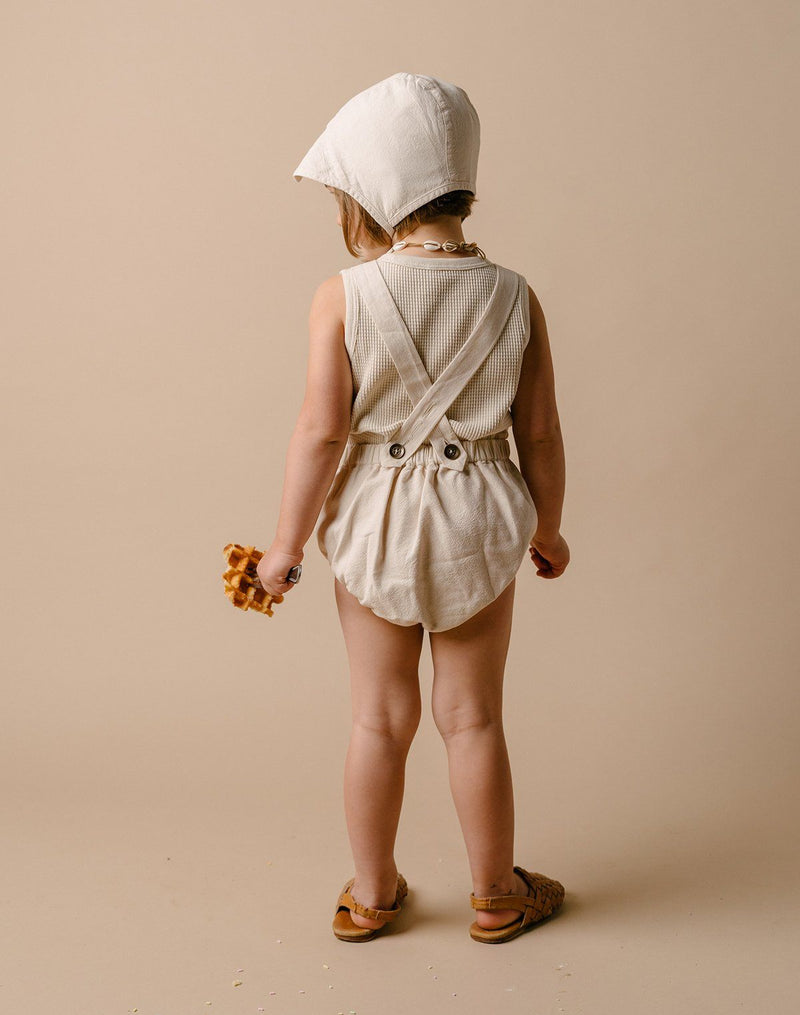 Back of a baby girl wearing an oat milk colored brimmed bonnet, sun suit and waffle tank top