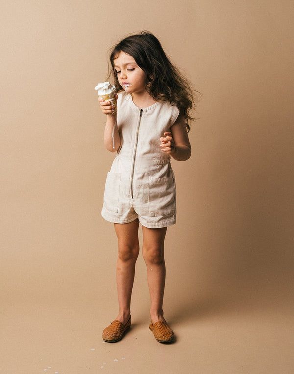 Kid with long hair eating an ice cream cone wearing the Noble Tank Suit in Oat Milk color