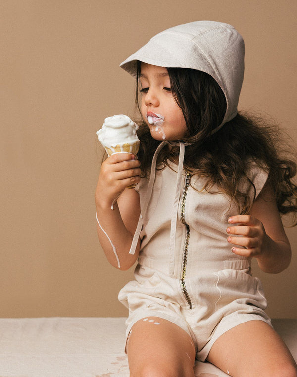 Baby sitting down eating an ice cream cone wearing a bimmed bonnet and tank suit in the oat milk color