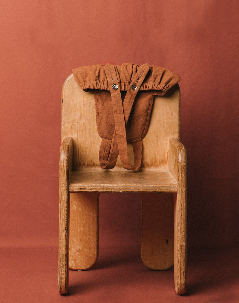 Noble Sun Suit in Cinnamon color draped over the back of a chair