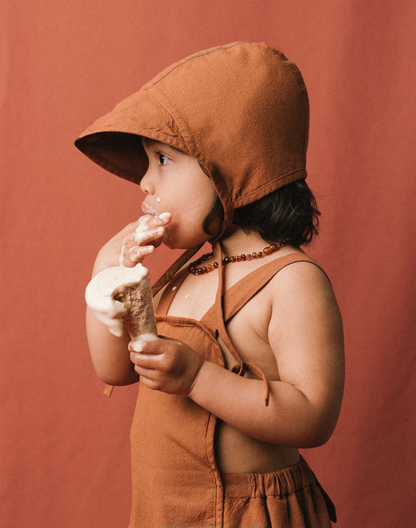 Baby licking an ice cream cone wearing a cinnamon colored brimmed bonnet and sun suit