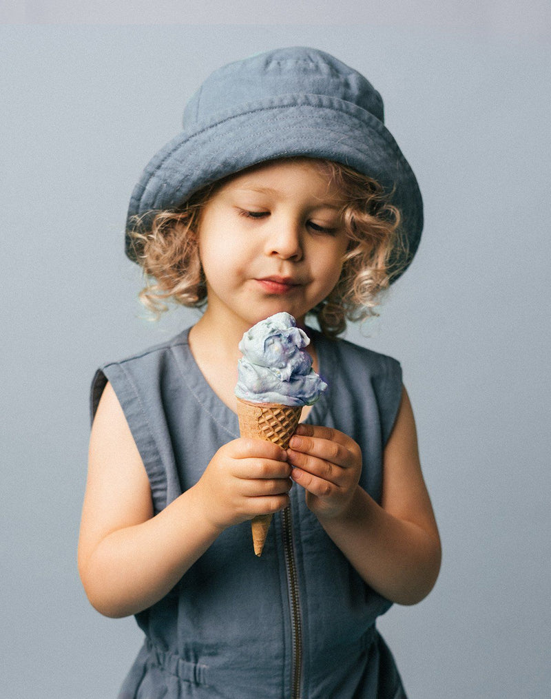 Baby eating a blue ice cream cone wearing a blue moon colored sun hat and matching tank suit