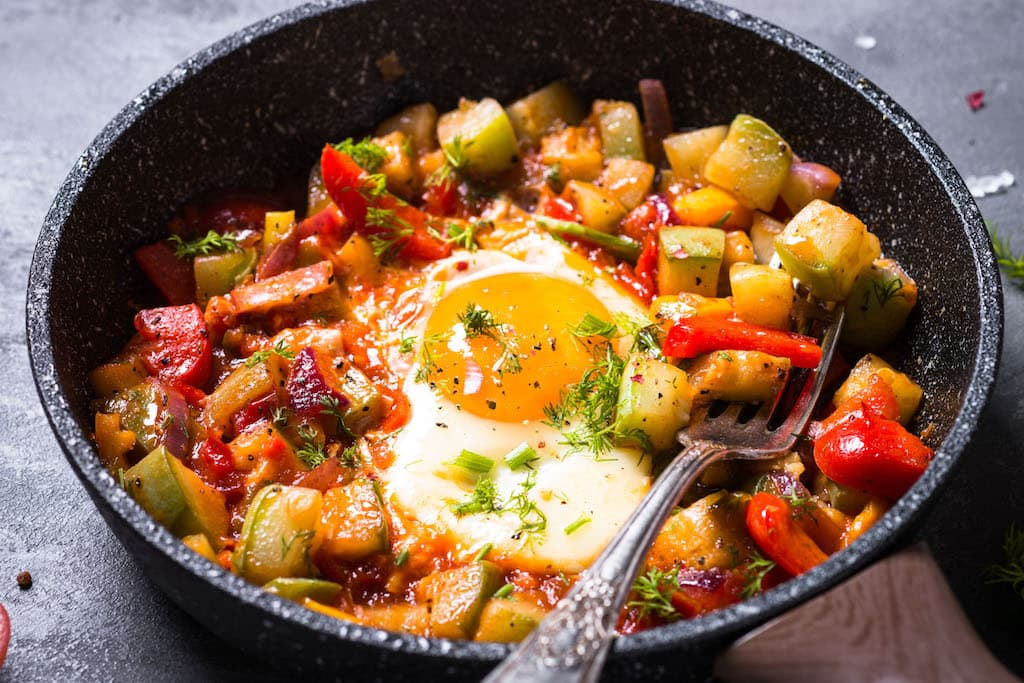Breakfast skillet with fried free-range eggs and vegetables