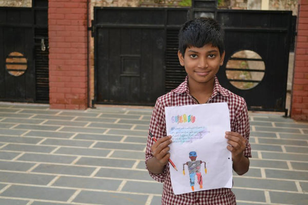 kid holding a superhero drawing