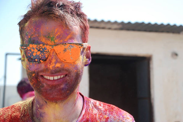 Guy wearing sunglasses with colorful powder during Holi party