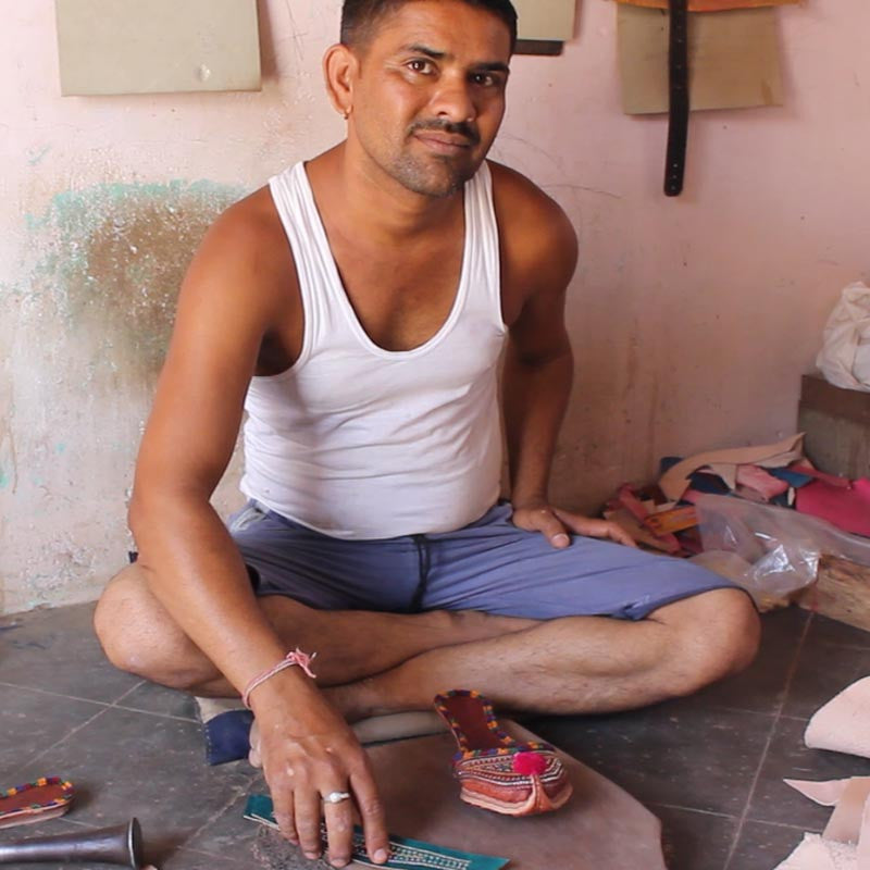 Indian artisan sitting with shoe