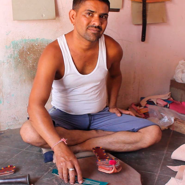 Indian artisan sitting on the floor making a shoe