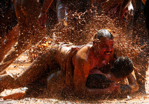 indian men playing in mud